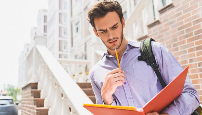 Pensive male student is studying with concentration. He is standing on street and holding open folder