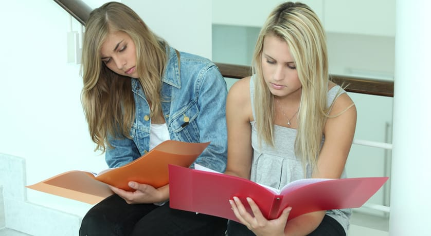 Two female students looking through work folders
