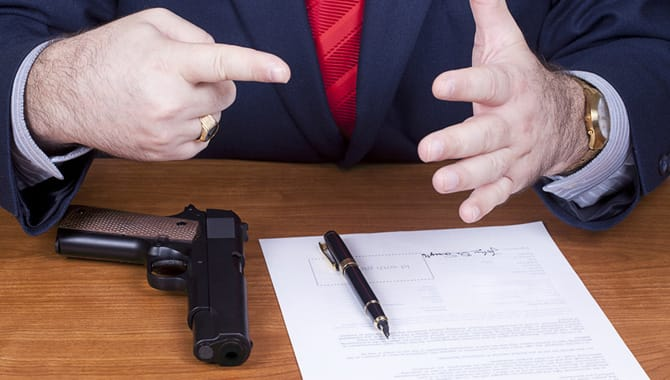 Businessman With A Gun Signing Contract