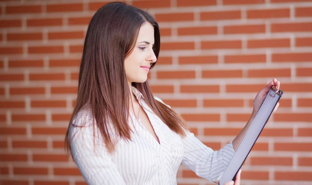 Smiling young elegant businesswoman with clipboard standing
