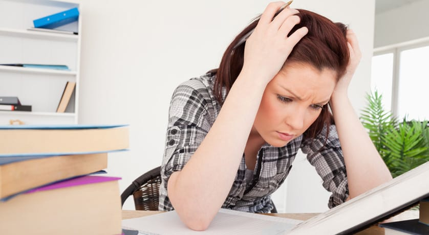 Attractive depresed female studying at her desk