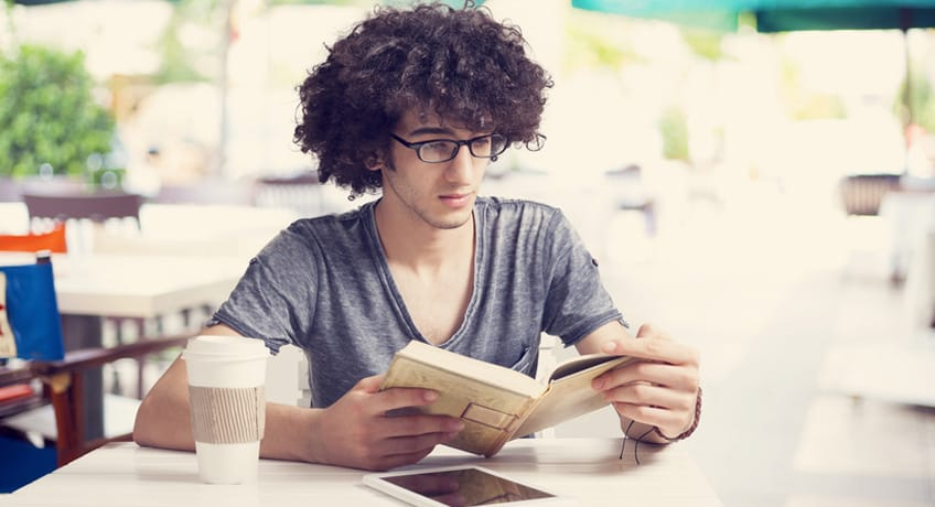 Young man reading book in cafe