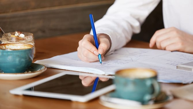 Close up of female student's hands holding a pen, writing an essay while doing homework at a coffee shop before going to the university. Education and technology concept. Selective focus on the hand