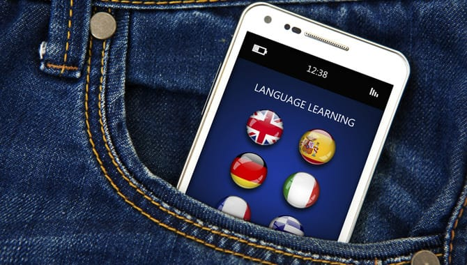 closeup of mobile phone with language learning application in jeans pocket. focus on screen